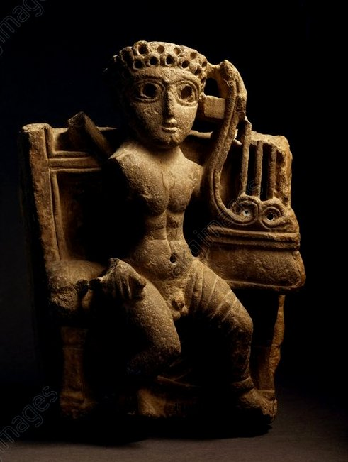 A damaged limestone sculture of a seated naked man with large eyes, curled hair, and a lyre in his left hand.