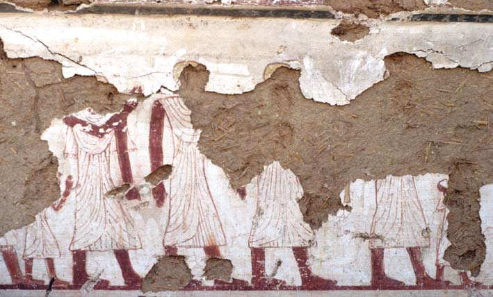Damaged fresco showing 7 figures in long white robes and shaved heads walking from the left to the right.