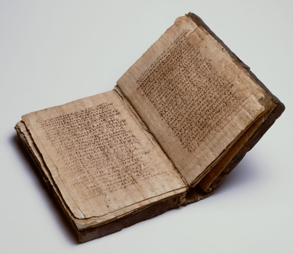 An image of an ancient codex (book) with a slightly damaged dark brown leather cover. Here the book is open to show the papyrus pages, with dense Coptic text on each side.
