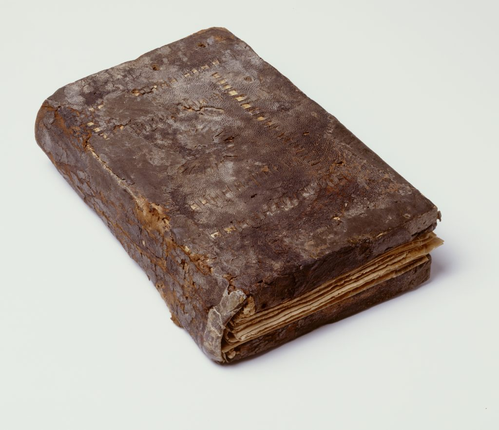 An image of an ancient codex (book) with a slightly damaged dark brown leather cover. Some decoration in the form of concentric rectangles with dotted lines is visible on the front. The papyrus pages are just visible although the book is closed.