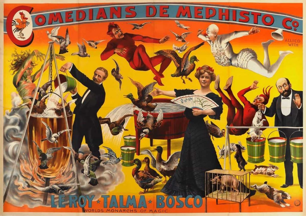 """An early 20th century poster for a magic show; in the middle a woman in a black dress holds a fan and gestures with her hand to a man on her right who is pouring water into a cauldron, out of which fly birds. On the left, another man has pulled a rabbit out of a bucket of water. A woman with wild hair stands over the cauldron, while birds and two figures, one dressed as a demon, the other dressed as a clown, fly over the scene. There is a caption: """"COMEDIANS DE MEPHISTO CO."""" written at the top, and at the bottom is written """"LEROY, TALMA, BOSCO WORLDS MONARCHS OF MAGIC""""."""