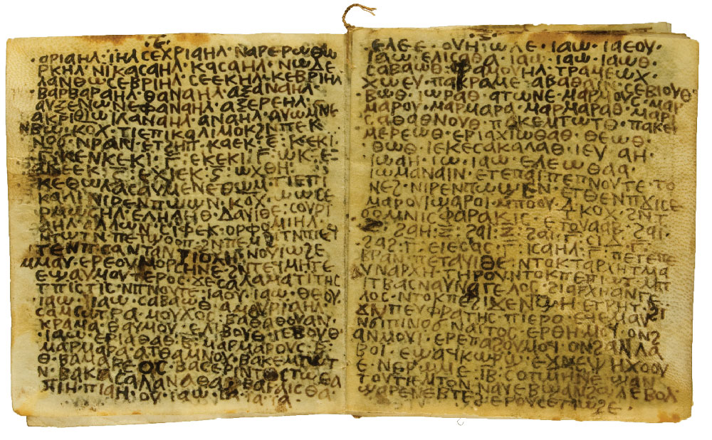 An open book on parchment written in Coptic. The pages are somewhat dark and stained.