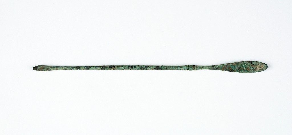 Image of a long thing copper spoon, slightly corroded.