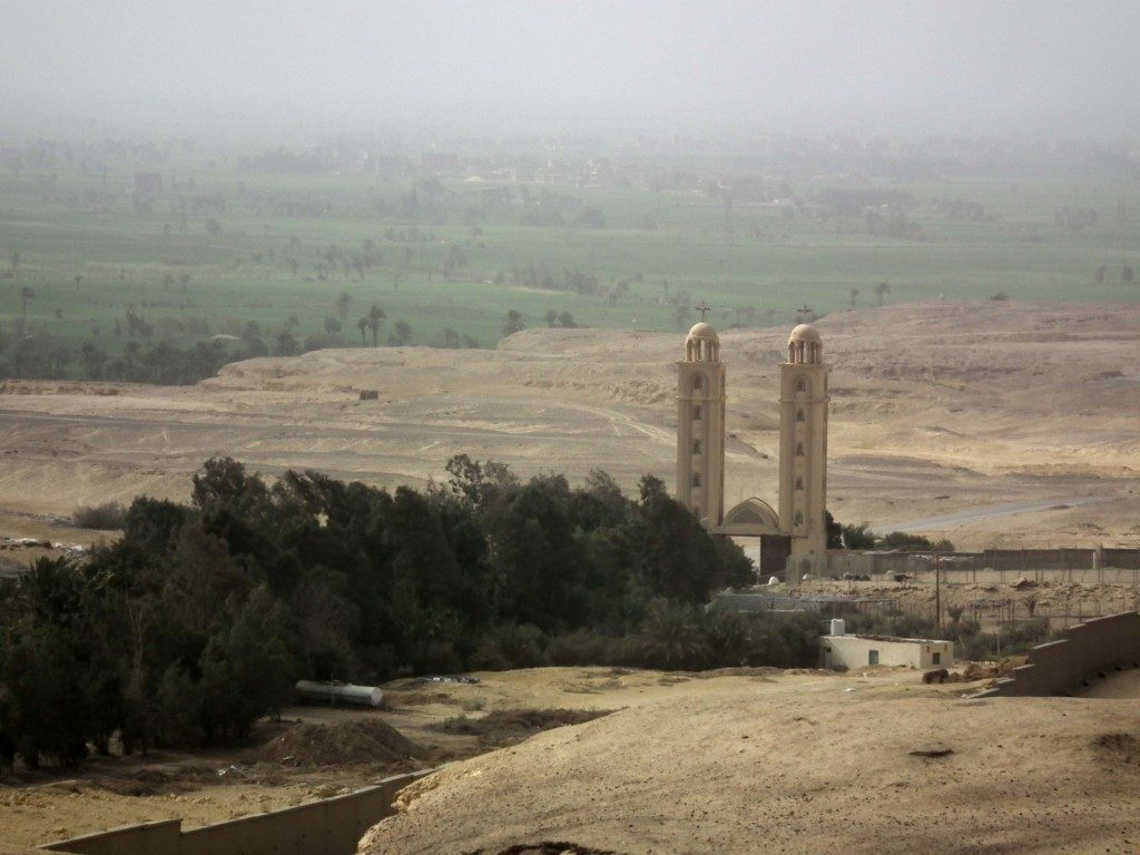A picture of a monastery with two towers in the Egyptian desert; in the foreground are a group of trees beside the monastery, while in the background the cultivated land of the Fayum can be seen.