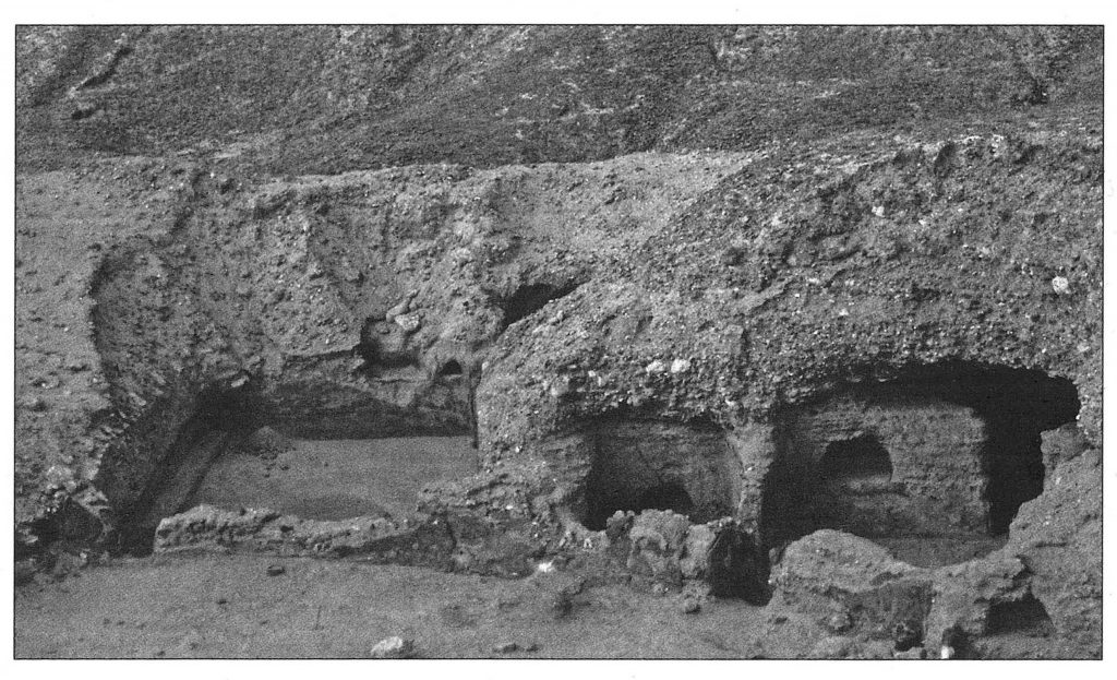 Black and white photograph of the remains of a monastery cut into the rock of a mountain, with walls and roofs supplemented by mud-brick.