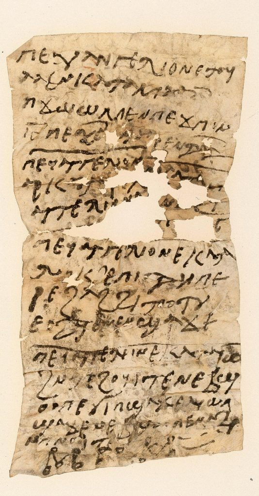 A tall, slim sheet of parchment, showing several horizontal and vertical folds, and considerable damage in the centre. It is covered with Coptic text, while at the bottom a few signs are visible, resembling Greek or Coptic letters, with circles drawn at each corner.