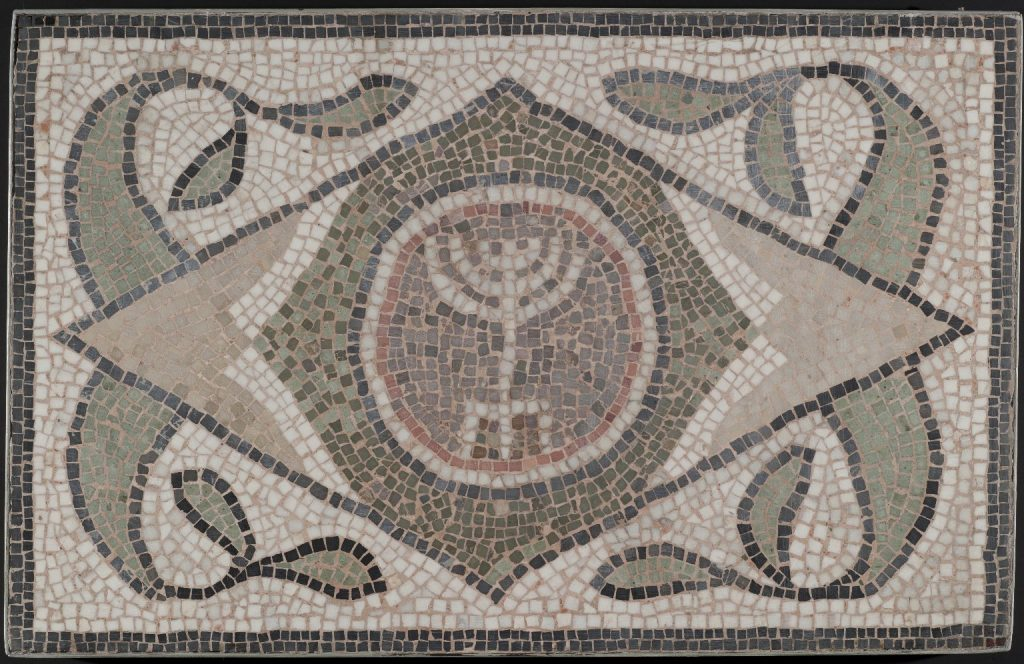 A mosaic showing a six-branched menorah with three legs within a diamond shape, decorated by curling plant-like forms.