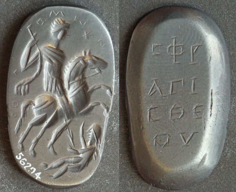 The front and back view of a dark grey, slightly glossy stone. The front is inscribed with the image of a man on a horse spearing a woman, with some Greek text above it. The back is inscribed with Greek text written in three lines.