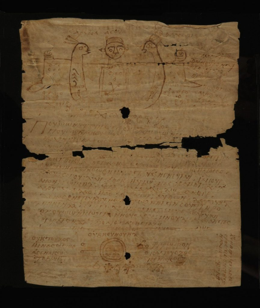 An image of a document on yellowed paper against a black background. At the top a figure can be seen facing forward, with a birdlike creature facing him on each side. Below this is Coptic text, and at the bottom can be seen a series of magical signs. Damage to the middle of the piece of paper suggests it was folded in half at one point.