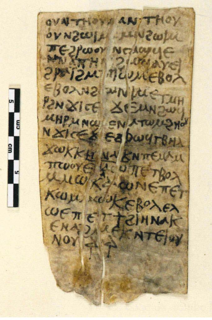 An image of a piece of yellowed paper with 16 lines of Coptic text written on it. The paper has been folded several times. A ruler to the left shows it is about 12 cm high and 6.5 cm wide.
