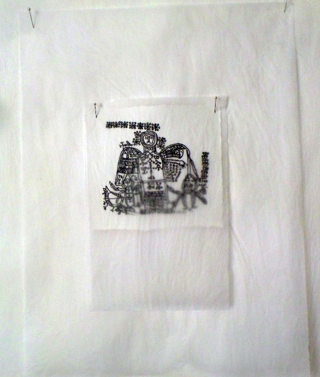 An image of a printing of a magical drawing of an angel surrounded by magical signs; the printed image, on white paper, is pinned to a wall through three larger pieces of tracing paper, and covered by one piece of tracing paper, through which is it still clearly visible.