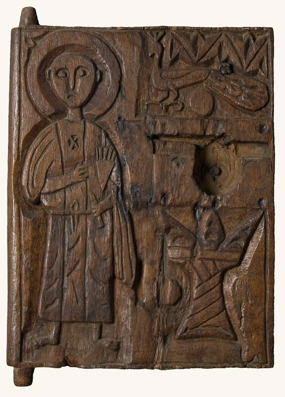 A wooden panel with tenons at the top and bottom left showing it was used as a door or lid. On the left is carved a figure in a monastic robe with a halo. On the upper right is a peacock, and on the lower right is a horned altar.