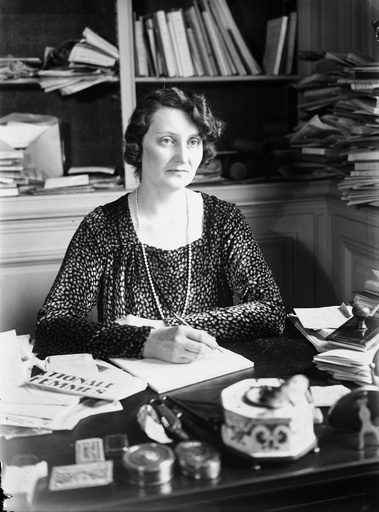 Black and white photo of a woman sitting at a desk and writing with a pen. In the background can be seen shelves piled with books and papers.