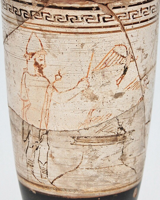 Image of part of a white pottery jug, with a bearded figure on the left in a pointed hat and cloak waving a wand over the opening of a very large jug set into the earth. Two very small winged figures fly out of it, while a third flies in.