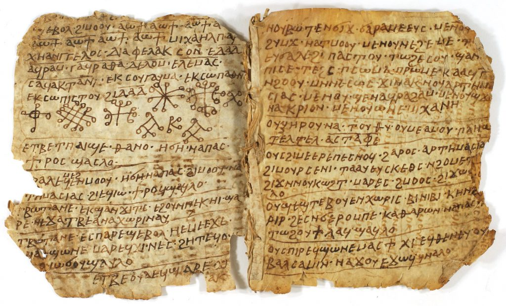 Image of a parchment codex, open to show two pages written with Coptic text and some magical symbols. There is some damage to the outer edges of the pages.